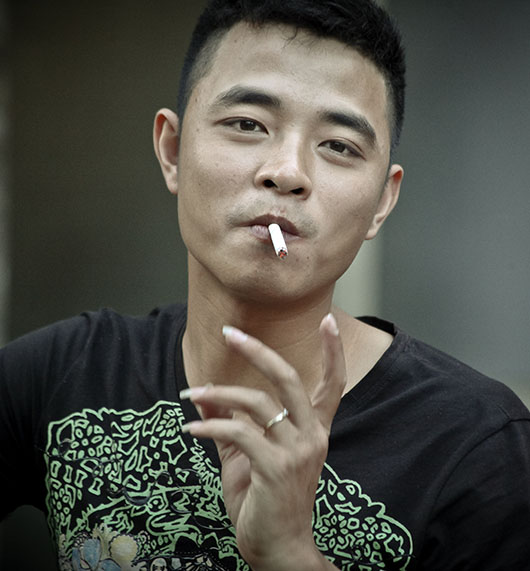 Jeune homme fume rue hanoi vieux quartier vietnam